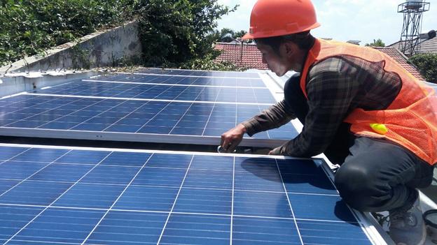 petugas jarwinn memasang solar panel di rumah pelanggan